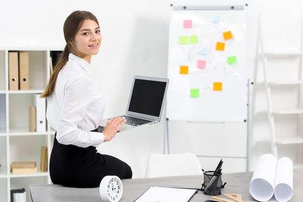 Empresaria sonriente que se sienta en el borde de la tabla que sostiene la tableta digital disponible que mira la cámara