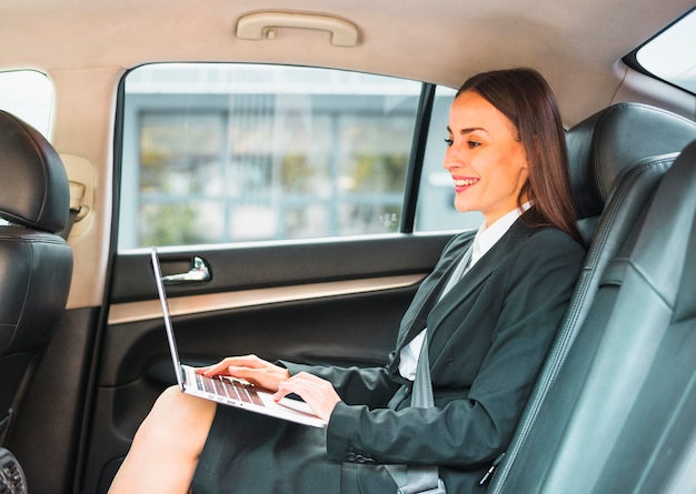 Empresaria sonriente que se sienta dentro del coche usando el ordenador portátil
