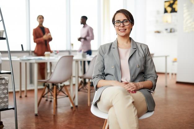 Empresaria sonriente que se sienta en silla