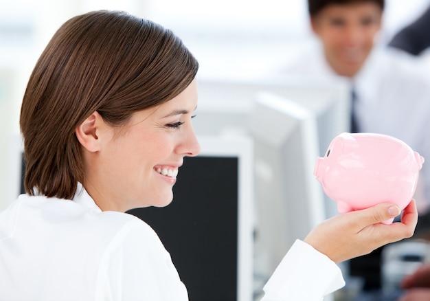 Empresaria sonriente que sostiene un piggybank