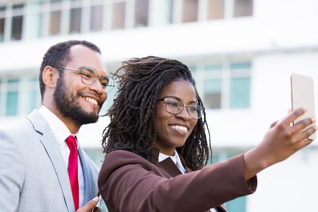 Empresaria sonriente que sostiene smartphone en brazo extendido