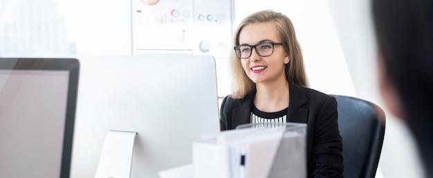 Empresaria sonriente que trabaja en el ordenador en fondo de la bandera de la oficina