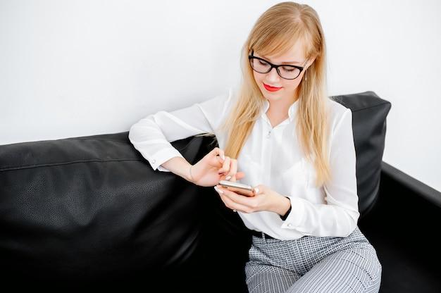 Empresaria sonriente que usa smartphone sobre fondo gris. vistiendo en camisa azul y gafas.