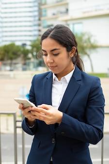 Empresaria sonriente que usa smartphone
