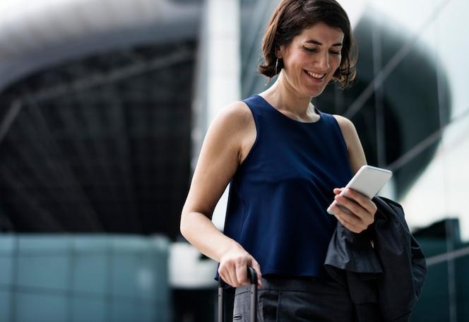 Empresaria sonriente que usa su teléfono
