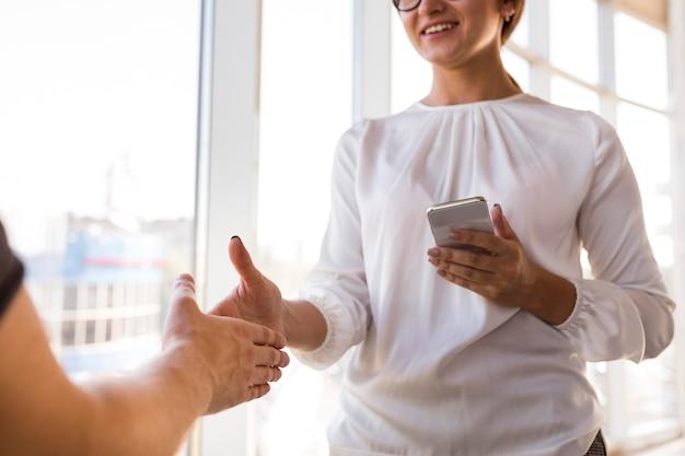 Empresaria sonriente saludando a alguien