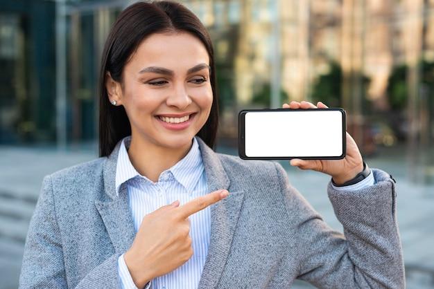 Empresaria sonriente sosteniendo y apuntando al teléfono inteligente
