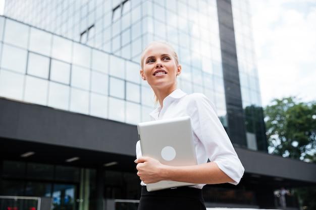 Empresaria sonriente sosteniendo tableta digital mientras mira lejos contra el edificio de oficinas