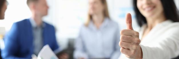 La empresaria sonriente sostiene los pulgares para arriba detrás de su equipo de empresarios