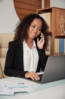 Empresaria sonriente con teléfono y computadora portátil