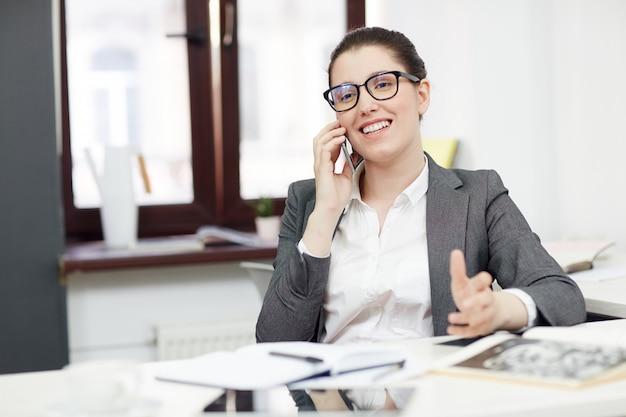 Empresaria sonriente con teléfono móvil