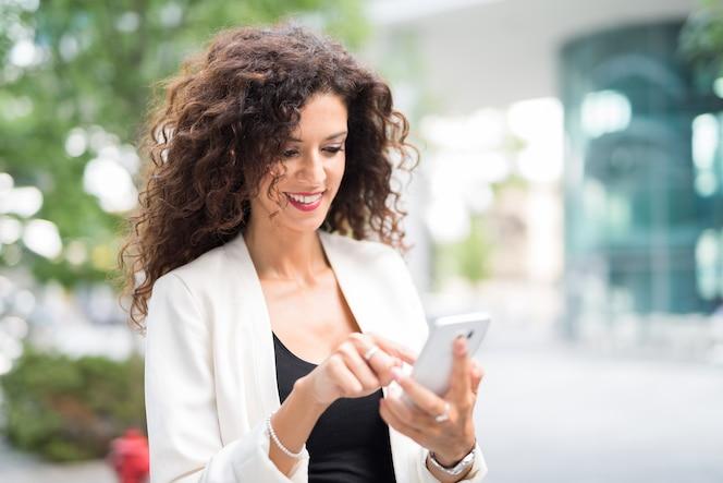 Empresaria sonriente usando su teléfono móvil