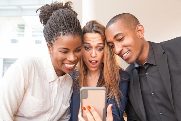 Empresaria sorprendida y colegas sonrientes tomando selfie