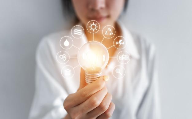 Empresaria sosteniendo bombilla incandescente, con iconos de recursos energéticos ecológicos