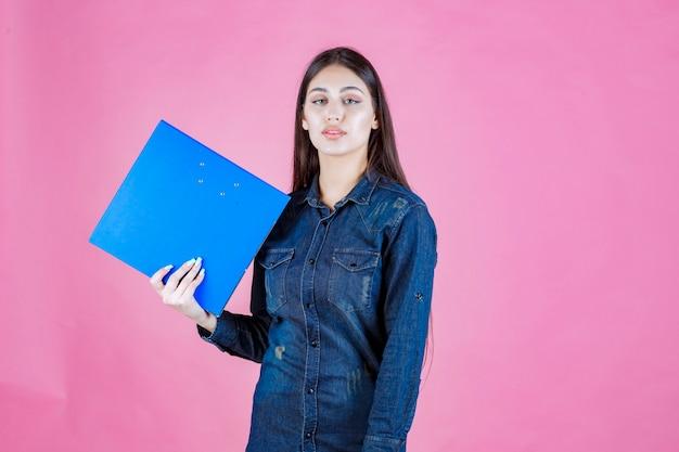 La empresaria sosteniendo una carpeta azul con confianza en sí mismo