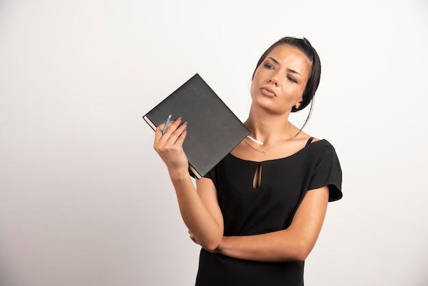 Empresaria sosteniendo el cuaderno mientras mira a un lado.
