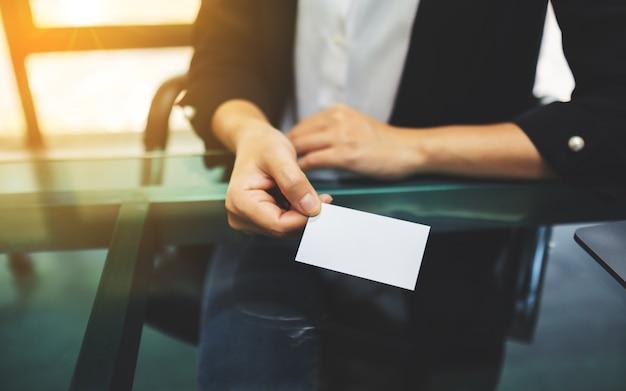 Empresaria sosteniendo y dando una tarjeta de presentación en blanco a alguien
