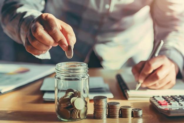 Empresaria sosteniendo monedas y poner en vidrio