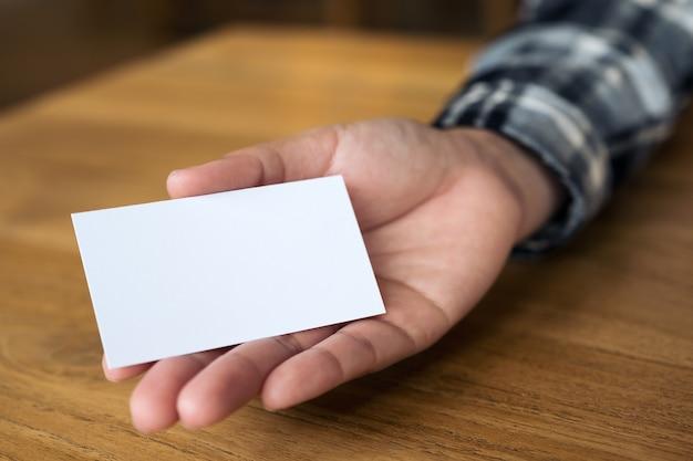Empresaria sosteniendo, mostrando y dando una tarjeta de visita en la mesa de madera