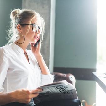 Empresaria sosteniendo periódico hablando por teléfono móvil