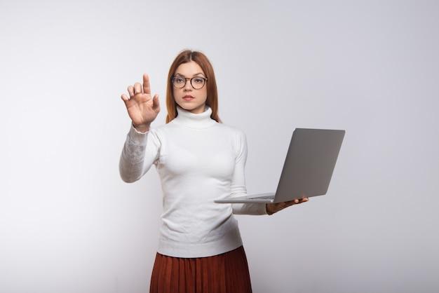 Empresaria sosteniendo portátil y tocar el aire con la mano