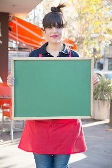Empresaria sosteniendo el tablero de menú verde en blanco en el café al aire libre