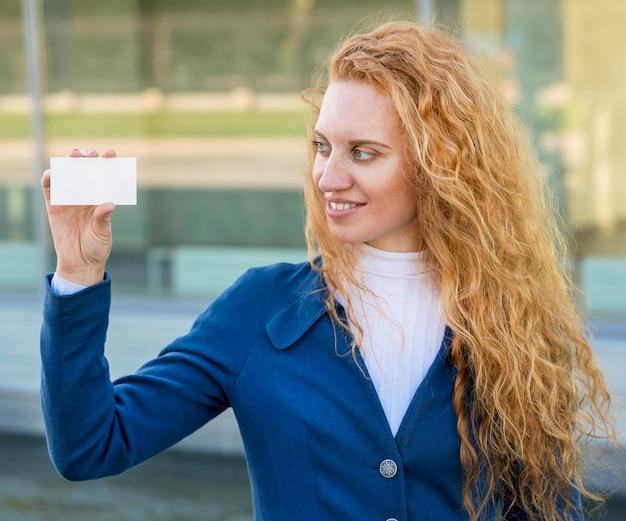 La empresaria sosteniendo una tarjeta de visita y mirando a otro lado