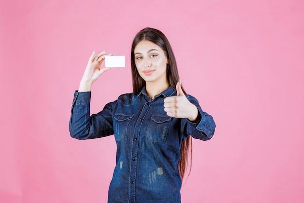 La empresaria sosteniendo la tarjeta de visita y mostrando el signo de la mano de disfrute