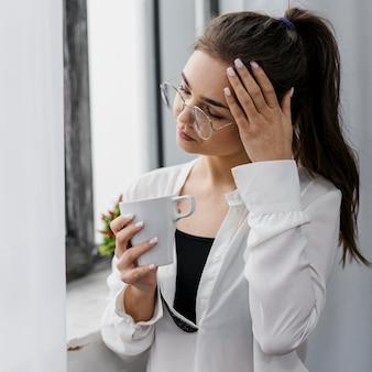La empresaria sosteniendo una taza de café mientras trabaja desde casa