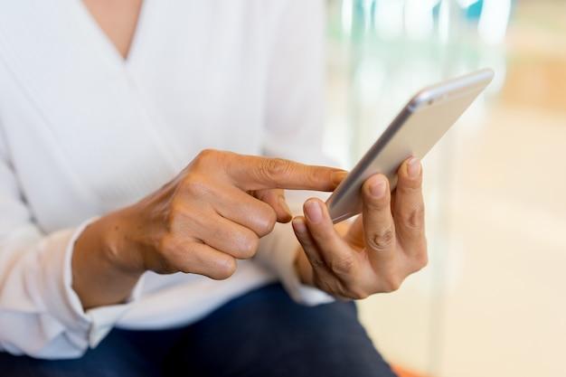 Empresaria sosteniendo un teléfono inteligente y revisando noticias de la compañía enviando mensajes de texto.
