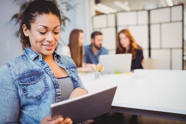Empresaria con tableta digital contra compañeros de trabajo
