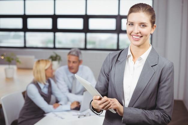 Empresaria con tableta digital en segundo plano en la oficina