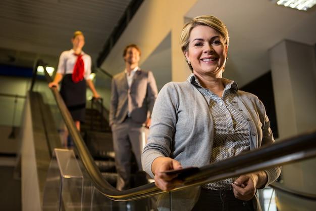 Empresaria con tarjeta de embarque de pie en la escalera mecánica