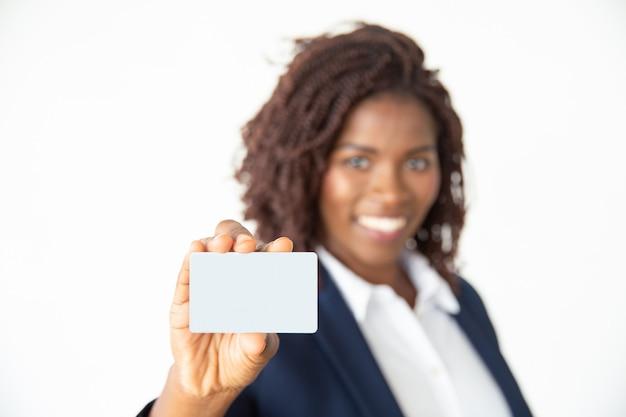 Empresaria con tarjeta y sonriendo a la cámara