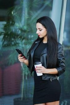 Empresaria con teléfono inteligente digital y tomar café cerca al lado del edificio de oficinas