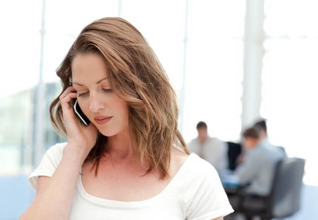Empresaria en el teléfono mientras su equipo está trabajando