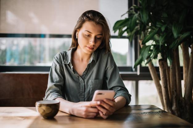 Empresaria mediante teléfono móvil, trabajando desde casa