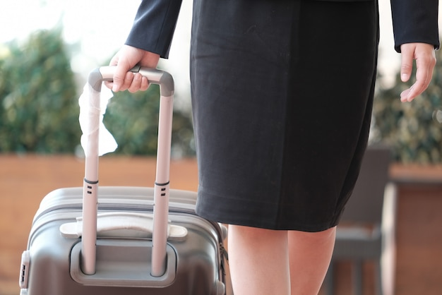 Empresaria tirando equipaje mujer llevando equipaje para viaje de negocios.