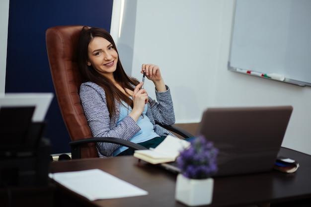 La empresaria toma tiempo en el trabajo descansando en una silla de oficina con la cabeza inclinada hacia atrás sobre las manos apretadas