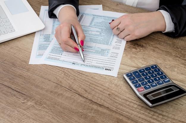 La empresaria trabaja con un formulario 1040 y una computadora portátil.