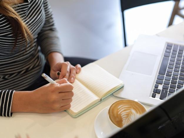 La empresaria trabaja durante la pausa para el café en la cafetería, computadora portátil, taza de café en la mesa