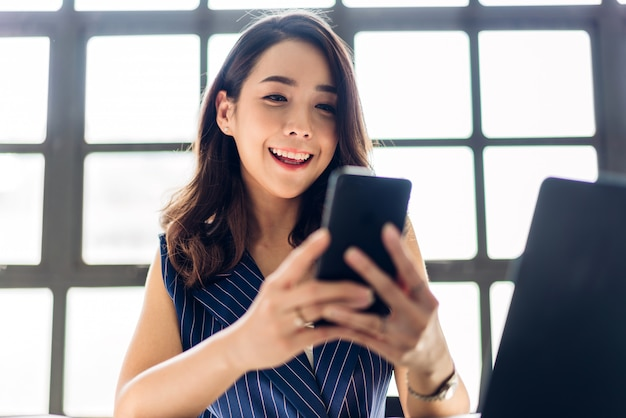La empresaria trabaja y usa el teléfono inteligente con una computadora portátil.creativos empresarios que planean en el loft de trabajo moderno