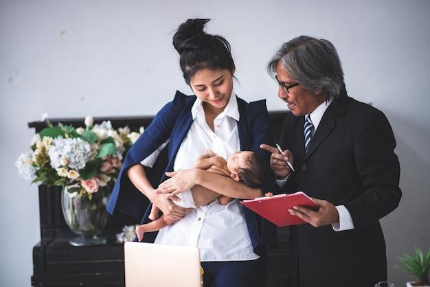 Empresaria trabajando desde casa, sosteniendo una niña