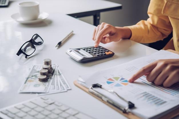 Empresaria trabajando en cuentas en análisis de negocios con gráficos y documentación.