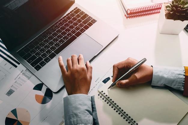 Empresaria trabajando en escritorio usando calculadora y laptop analizando finanzas
