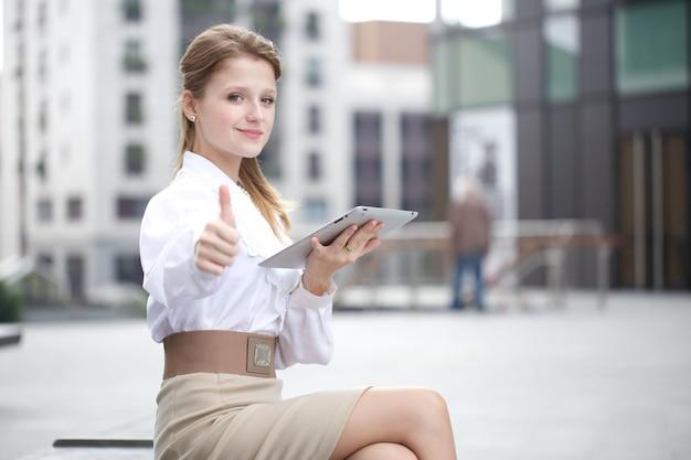 Empresaria trabajando fuera del edificio de oficinas con dispositivos digitales