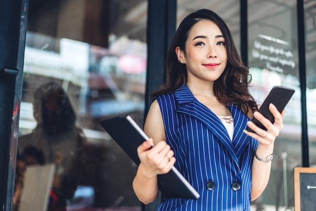 Empresaria trabajando y usando el teléfono móvil mientras está de pie delante del café