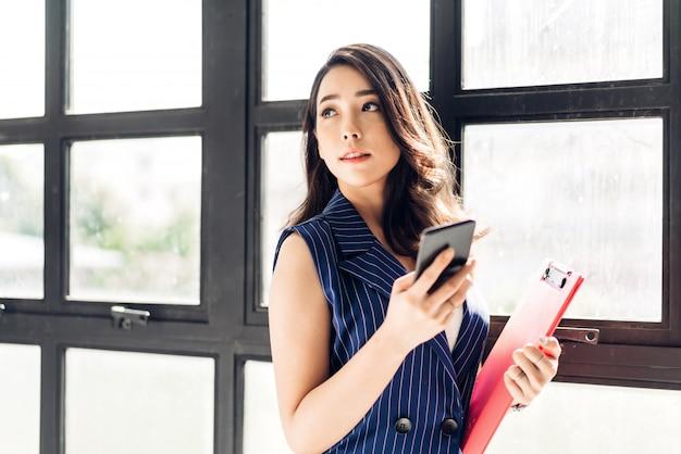 Empresaria trabajando y usando el teléfono móvil mientras está de pie en la oficina