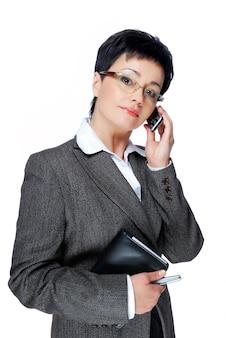 La empresaria en traje gris llamando por teléfono móvil