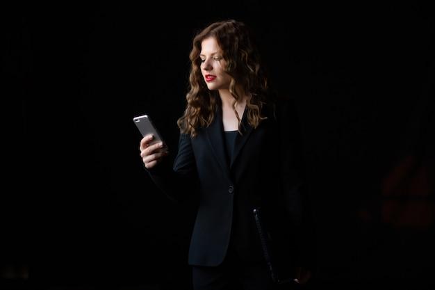 La empresaria en un traje negro con cabello rizado y labios rojos está usando un teléfono inteligente sobre fondo negro
